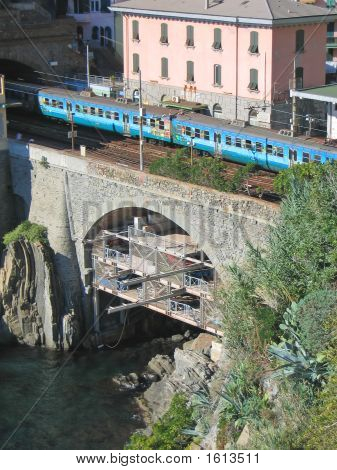 Blue local train passing a bridge over the sea in Riomaggiore village - The Cinque Terre - Italia. poster