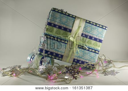 Christmas gift boxes with ribbons and garlands, festive lights on a white background