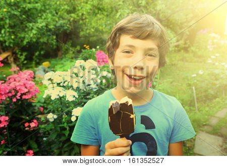 preteen handsome boy with sun tan and escimo icecream close up portrait in green garden with flowers