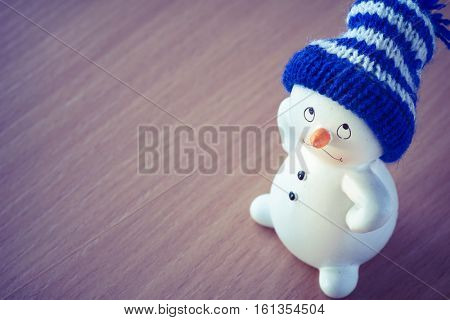 Happy Cute Snowman on Wooden Table, Christmas and New Year Greeting Cards, Christmas Gift Tag, Merry Christmas! Cheerful Christmas Toy Snowman on a Wooden Background