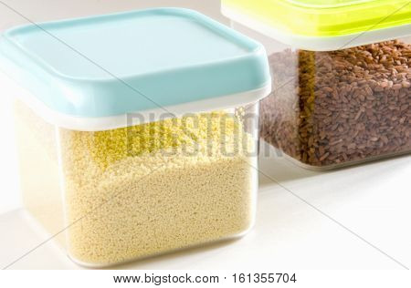 Food storage. Food ingredients (cous cous and brown rice) in plastic containers. Selective focus.