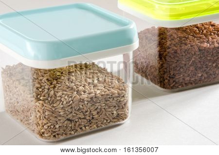 Food storage. Food ingredients (spelt wheat and brown rice) in plastic containers. Selective focus.