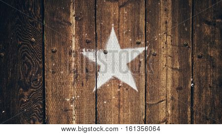 White star shape stencil painted on old vintage retro wood background.