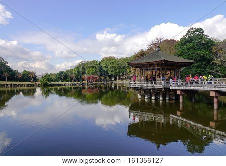 Tourists On The Wooden Pavilion Over A Pond