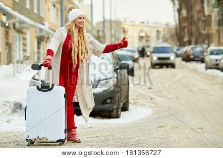 Young woman with trolley bag tries to catch cat on snow-covered road.