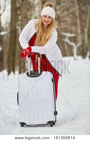 Young woman with white trolley bag stands in winter park.