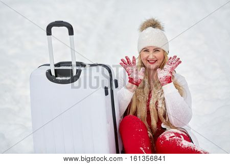 Young smiling woman sits near trolley bag, showing hands in gloves covered by snow in winter park.