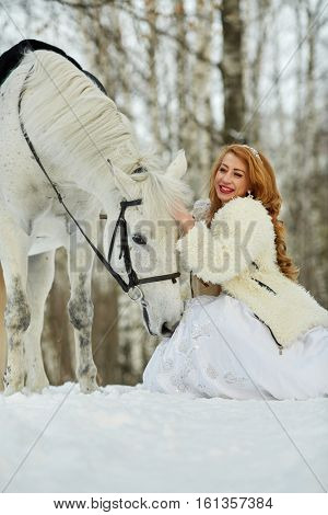 Young smiling woman in white dress and white fur mantle strokes white horse in park.