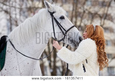 Young woman in white fur mantle kisses white horse in park.