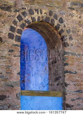 Arched window detail of the Campanile or bell tower revealing a blue wall at Portmeirion Wales.