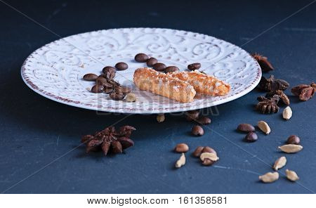 a a sugar cookies on a vintage saucer with ornament spice anisetree and cardamom on a dark surface