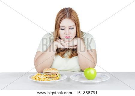 Portrait of overweight woman looks doubtful to choose a fresh apple fruit or hamburger isolated on white background