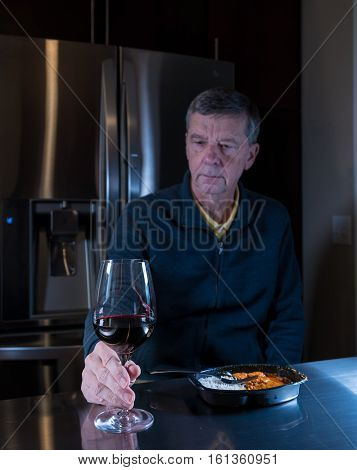 Lonely and depressed senior male sitting alone at kitchen table eating a microwaved ready meal of curry with red wine