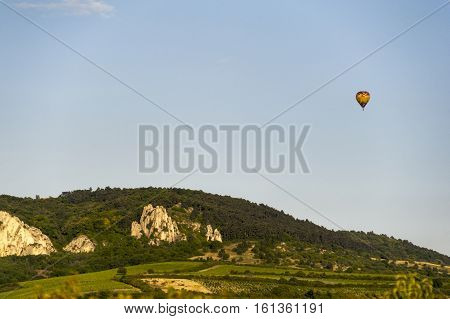 Colorful hot air balloon flying over rocky mountains and winery on Summer evening with clear blue skies. South Moravia Czech Republic.