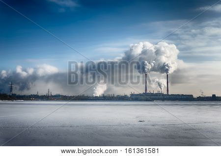 Power plant smokes in blue dramatic sky in a winter city. Free copyspace for text. Horizontal image HDR