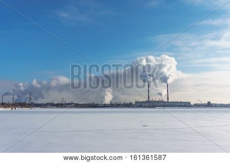 Power station with pipes of which poured smoke on a frozen river. Free copyspace for text. Horizontal image.