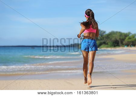 Woman runner running barefoot on sand at beach. Female athlete with slim legs jogging away, view from the back, on tropical travel destination.