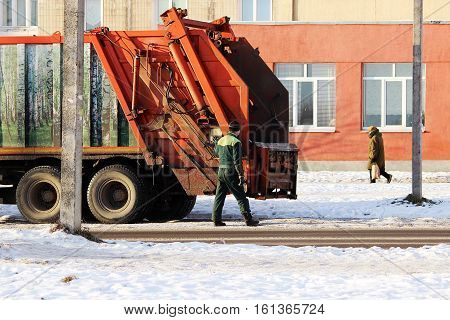 Worker standing next to a junk car after loading garbage tank