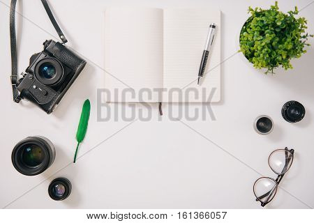 Workspace of a photographer. Flat lay of a green feather being surrounded by camera lenses while near the open notebook