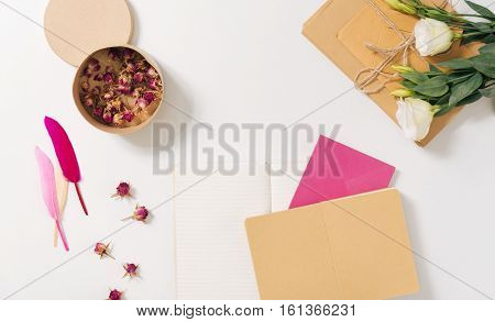 Beautiful and aesthetic. Round small paper box being filled with dried roses and standing on the white desk near envelopes poster