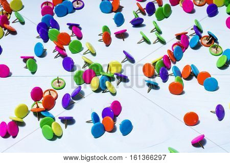 Colorful push pins on blue wooden background close up. Bright multi-colored thumbtacks.