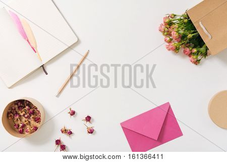 Shades of pink. Top view of pink envelope lying near scattered rose buds while being ready to be sent