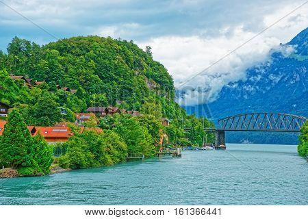 Brienz, Switzerland - August 25, 2014: Bridge over the Lake Brienz and Brienzer Rothorn mountain on the background at Interlaken in Canton of Bern in Switzerland