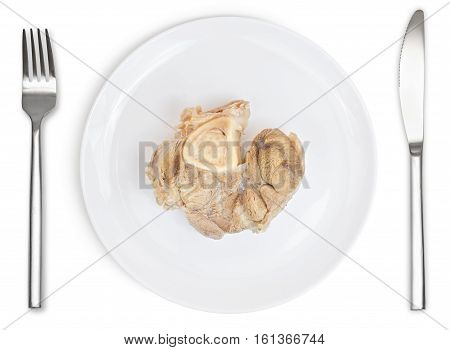 Boiled pork on plate with knife and fork isolated on white background. Animal food.