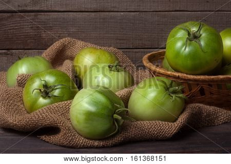unripe green tomatoes in a wicker basket on wooden table with sacking.