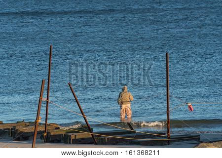Fisherman knee deep in Blue Ocean Water dressed for a cold wintry day