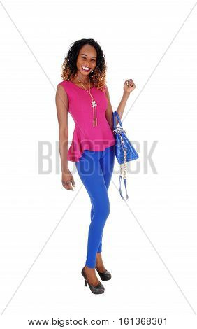 A beautiful young African American woman in blue tights and purse and a dark pink blouse standing isolated for white background.