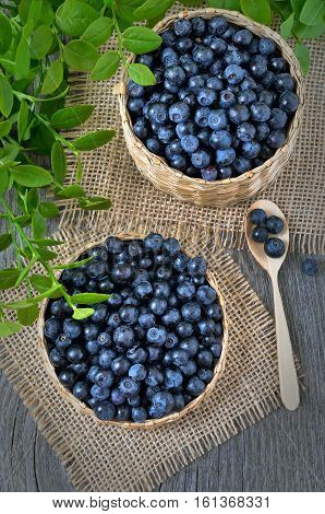 Fresh bilberry in a wicker basket on wooden table top view