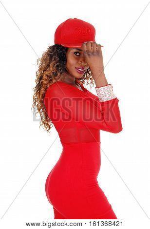A lovely young African American woman in a tight red dress and red cap standing in profile isolated for white background.