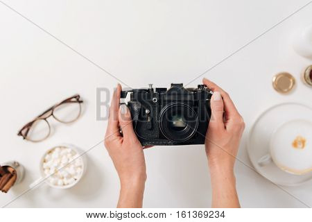 Taking a selfie. Flat lay of a vintage photo camera being in hands if a nice young female photographer while taking a selfie