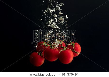 Tomatoes cherry in the water with air bubbles
