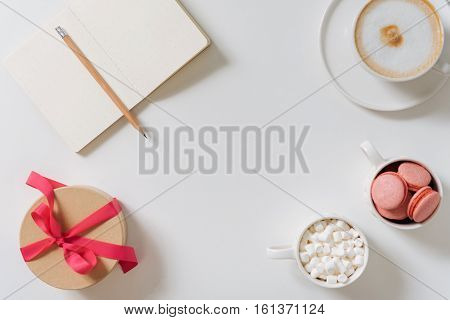 Valentines present. Gift box tied with pink ribbon and standing near the open notebook while preparing to be presented for Valentines Day