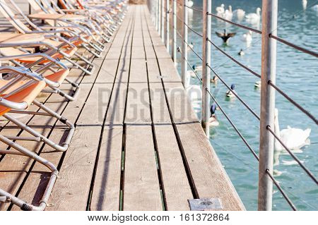 wooden pathway with sunbeds along lake bank