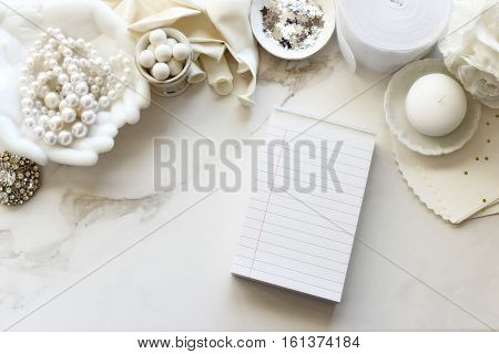 Chic ivory and white bridal accessories frame desk top with a blank notepad.