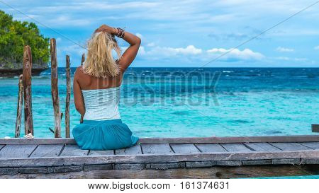 Girl Staying on Wooden Pier of an Homestay looking into blue ocean, Gam Island, West Papuan, Raja Ampat. Indonesia
