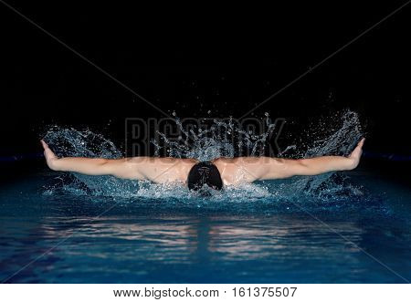 Young man in black cap in swimming pool. Butterfly style