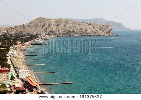 SUDAK, CRIMEA - AUG 15, 2013: Sudak Bay. Summer day on the beach in Sudak