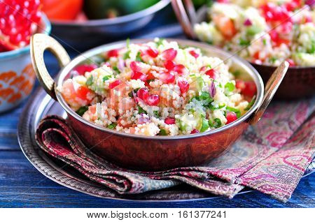 Healthy salad with couscous, tomato, avocado, red onion, pomegranate and olive oil. Eastern cuisine.