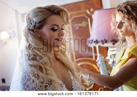makeup artist preparing bride before the wedding