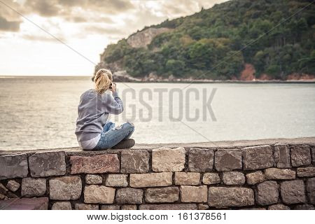 Woman traveller making mobile photo of picturesque landscape during travel holidays sitting on old wall during sunset at beach