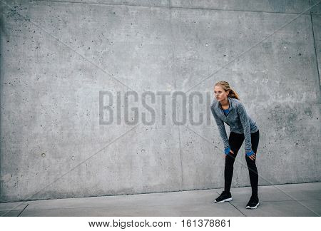 Young Woman Taking A Break From Exercise Outdoors