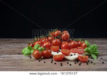 Scattered cherry tomatoes and pepper balls with leaves of basil on the wooden table.