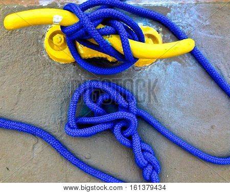 yellow cleat hitch with a blue line in knots at the dock