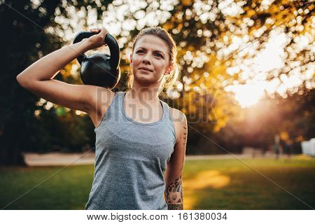 Portrait of fit young woman with kettlebell weights in the park. Fitness woman training with weights in park.