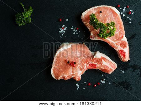 Raw pork steaks crude cutlets with bones and fresh parsley on black stone background top view.
