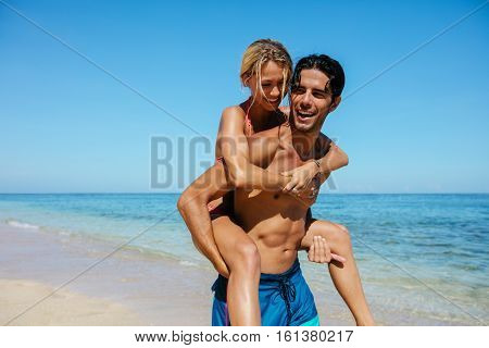 Portrait of man carrying girlfriend on his back. Couple enjoying piggyback ride on the beach vacation.